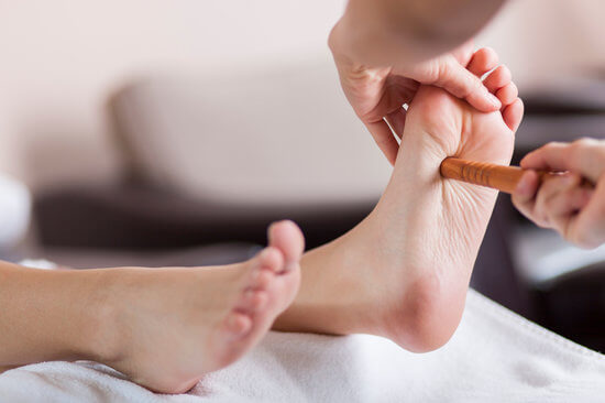 Massage therapist using Reflexology techniques